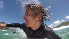 SLOW MOTION CLOSE UP: Cheerful young surfer doing duck dive Stock Footage