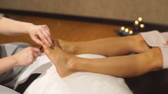 Women at reflexology having foot massaged or pressed with wooden stick Stock Footage