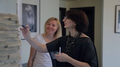 Two women stand in front of large sheet of paper and write something Stock Footage