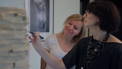 Brunette home stylist draws fashion concept sketch to blonde client Stock Footage