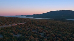 Aerial - Coastal road on island Cres at sunset with a view toward Osor town Stock Footage
