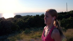 Stabilized shot - Smiling young sporty woman recreational running at the seaside Stock Footage