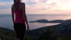 Beautiful adult woman standing on top of the seaside mountain and raising arms Stock Footage