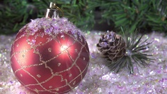 New Year's balls lie on snow against the background of a Christmas fir-tree Stock Footage