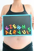 Young expectant mother with magnetic letters choosing a name for her baby Kuvituskuvat