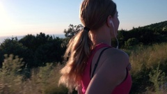 Stabilized shot - Behind young sporty fit woman running at the seaside at sunset Stock Footage