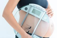 Weight gain during pregnancy with pregnant woman holding scale Stock Photos