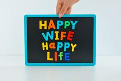 Happy wife happy life with magnetic colored letter blocks on blackboard Stock Photos