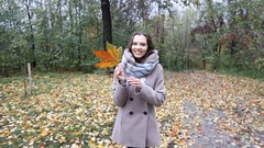 Happy pretty girl with big colored maple leaf in the fall forest or park Stock Footage