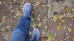 Feet, wearing blue shoes, walking on a park road, covered with fall leaves Stock Footage