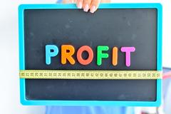 Measure your profit concept written as colored magnetic letter blocks with scale Stock Photos