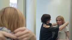 Stylist helps to create image with scarf in front of mirror Stock Footage