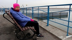 Girl sitting on a bench on the pier on a cold cloudy day looks into the camera Stock Footage
