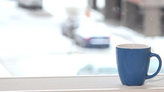 Cup of coffee tea hot drink on window sill and snowflakes snow fall outdoor Stock Footage