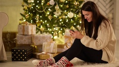 Young Woman Sitting on the Floor with Black Smartphone on Background Christmas Stock Footage