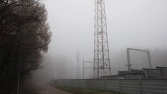 Electric power lines constructions in a foggy dark morning Stock Footage