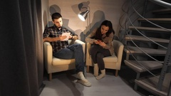 Bored couple online with their smart phones sitting on a chairs in the living Stock Footage