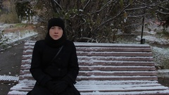 Portrait of a girl in a black dress, sitting on a bench in the park in winter Stock Footage