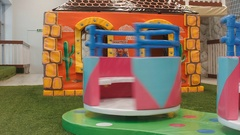 Children round the carousel turns in the play area. Little girl climbs on it Stock Footage