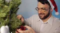 Fashionable man wearing a Santa hat decorates the Christmas tree on new year Stock Footage