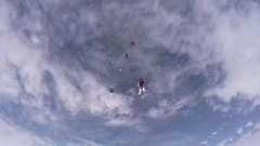 Skydivers jump from airplane, make formation in cloudy sky. Dangerous. Teamwork Stock Footage