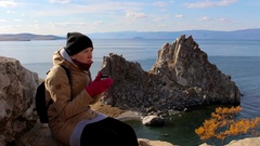 Girl sits on a rock by the sea on a background of amazing landscape, drinks tea Stock Footage