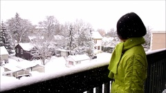 Winter scene, woman watching snow  on balcony Stock Footage