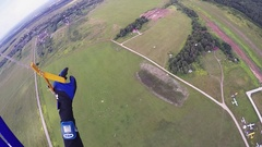 Professional skydiver on parachute fly down to green field for landing. Extreme Stock Footage