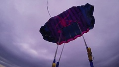 Professional skydiver opening parachute in air fly over green field. Extreme Stock Footage