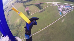Professional skydiver on parachute fly over green field, forest. Extreme sport Stock Footage