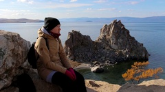Girl sitting on a rock by the sea on a background of amazing landscape. Stock Footage