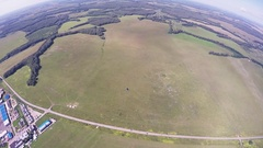 Professional skydiver on parachute fly over green field among others. Landscape Arkistovideo
