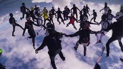 Skydivers make big formation in cloudy sky. Dangerous flight. Teamwork. Sport Stock Footage