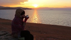 Girl sits on the shore of the sea and drinks a hot tea. Amazing golden sunset Stock Footage