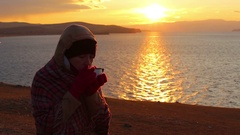 Girl sits on the shore of the sea and drinks a hot tea. Beautiful golden sunset Stock Footage