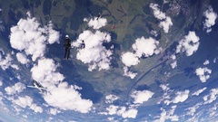 Professional skydivers jump from airplane, parachuting in clouds. Sunny day Arkistovideo