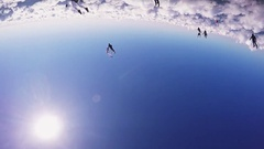 Professional skydivers parachuting, make formation in air in sunny day. Clouds Stock Footage