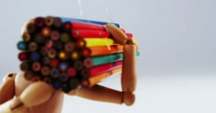 Figurine carrying bunch of colored pencil Stock Footage