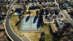 Aerial view of a park, path, tennis courts, neighborhood Stock Footage
