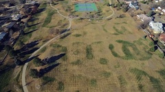 Aerial view of a pair of tennis courts in a yard in a residential community Stock Footage