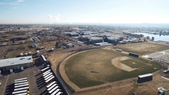 Aerial of a baseball diamond, industrial area, streets, fields, parking Stock Footage