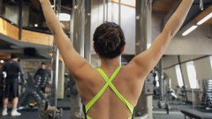 Woman pumps iron in Fitness-station. View from her back Stock Footage