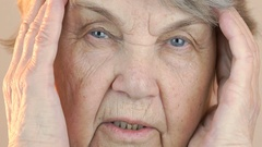 Old woman holding head with hands due to headache Stock Footage