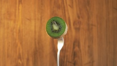Fork With Kiwi on Wooden Background Stock Footage