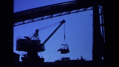 1971: crane lifting a bulldozer into the air at construction site MAINE Stock Footage