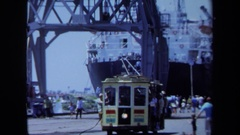1971: tram driving on a dock with huge cranes and a dry-docked ship MAINE Stock Footage