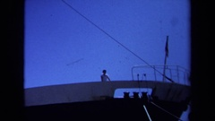 1971: a man standing on top of a large navy ship while people walk pass. MAINE Stock Footage