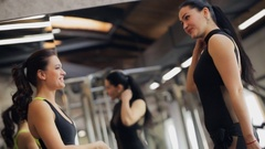 Two women in the sport black suit talking and smiling at the gym Stock Footage