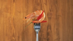 Rotating Fork With Prawn and Chili Pepper on Wooden Background Stock Footage