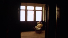 1971: an elderly woman reclining in a chair next to a window LONG BEACH Stock Footage